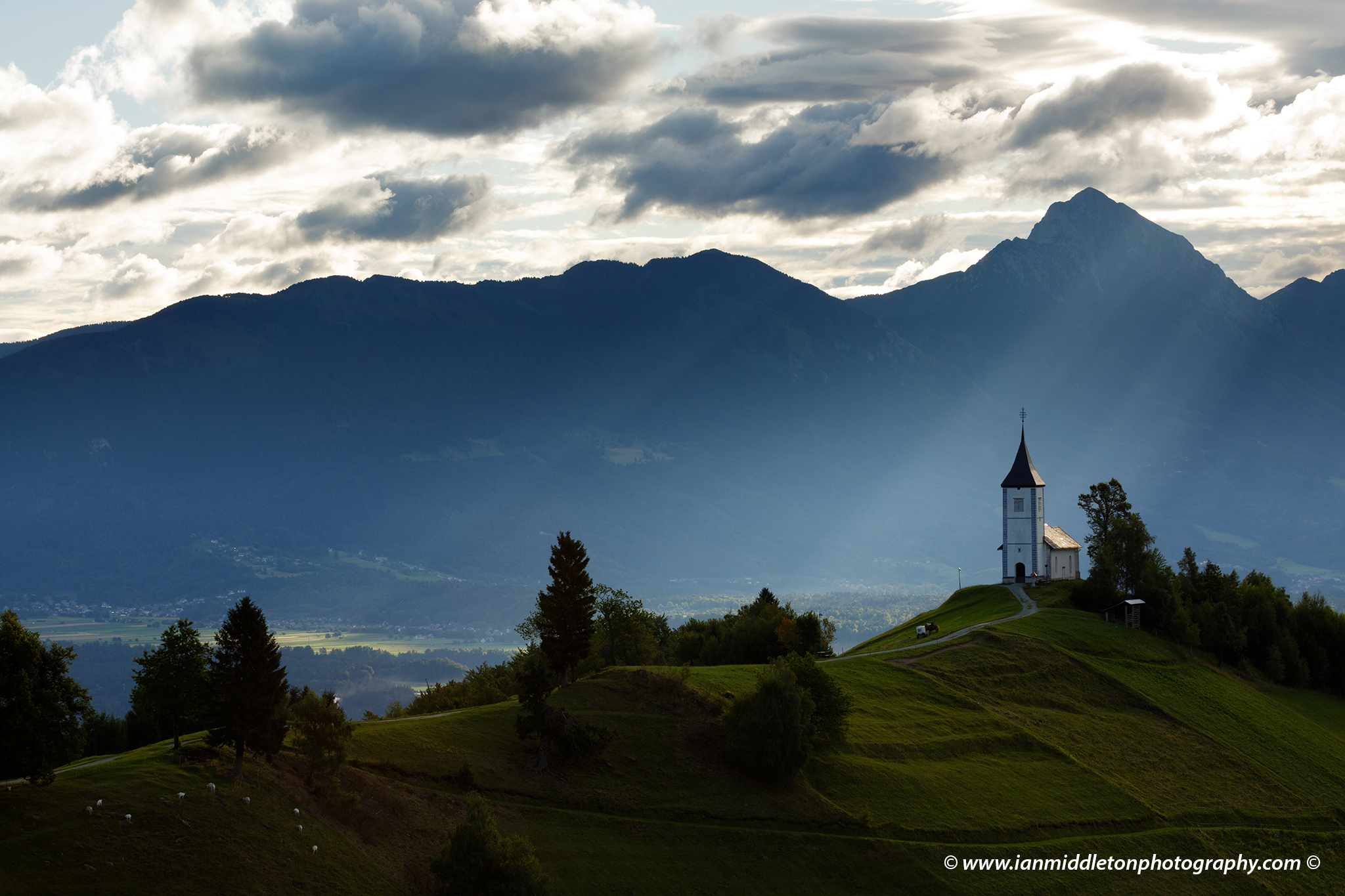 Jamnik church of Saints Primus and Felician, perched on a hill on the Jelovica Plateau with the kamnik alps and Storzic mountain in the background, Slovenia.