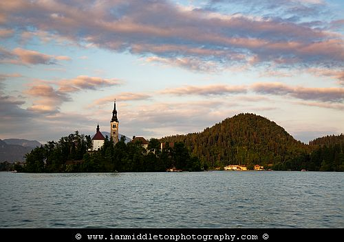 Sunset at Lake Bled's island church with the Karavank Mountains behind, Slovenia.