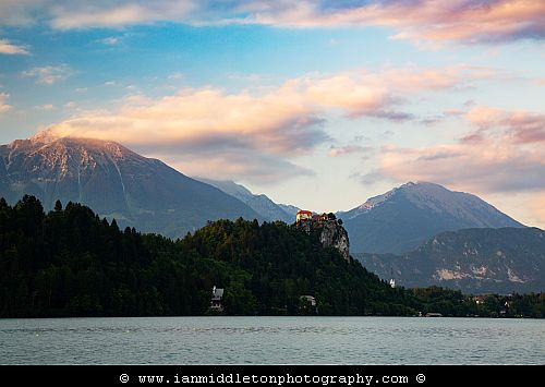 Beautiful light across the beautiful Lake Bled's hilltop castle and Mount Stol, the highest peak in the Karavank Mountains. Slovenia.