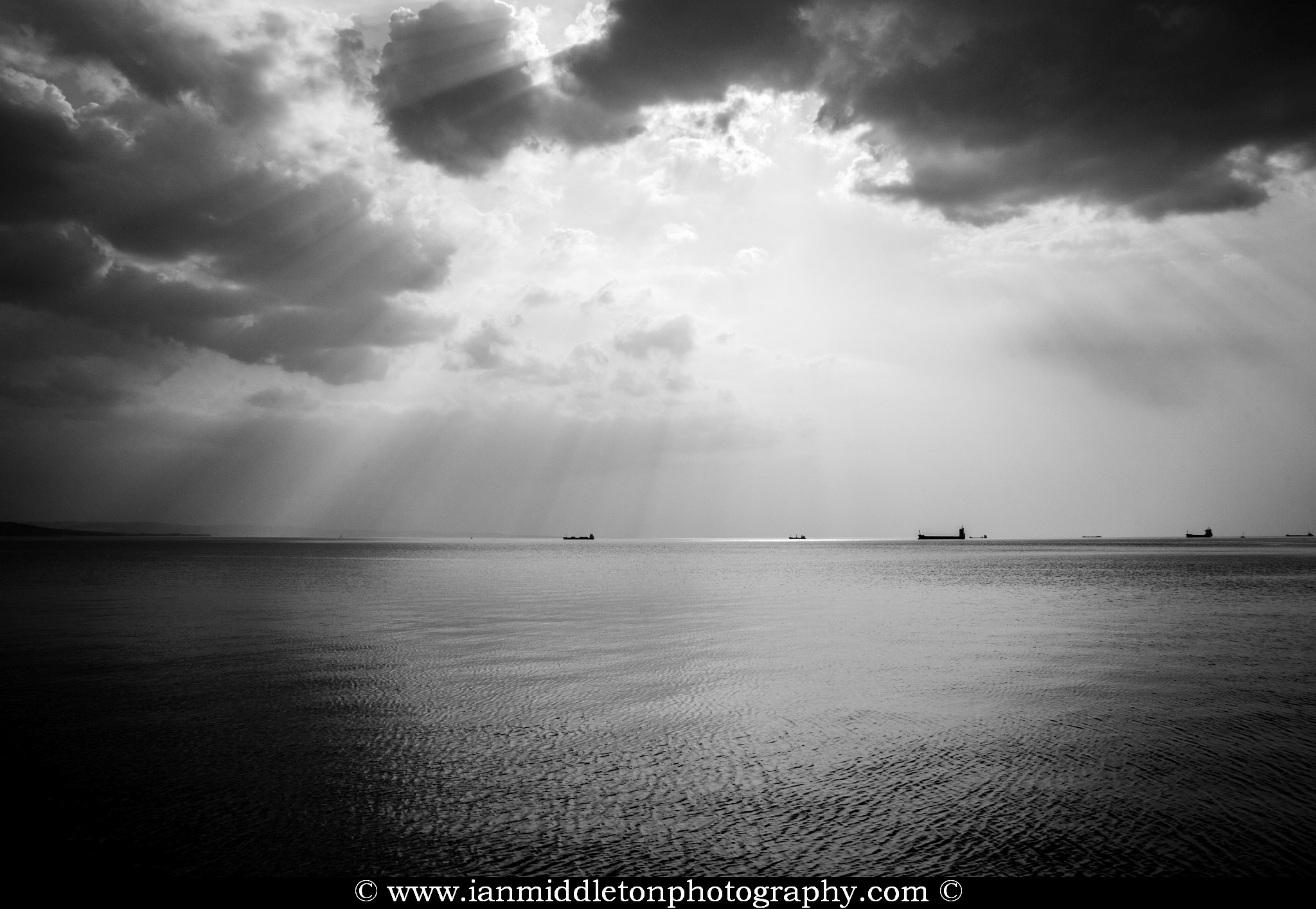 Scattered clouds produce beautiful rays of sunlight over the ships entering and leaving trieste Bay, Italy.