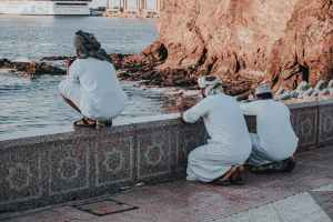 arab men in white traditional wear praying on embankment