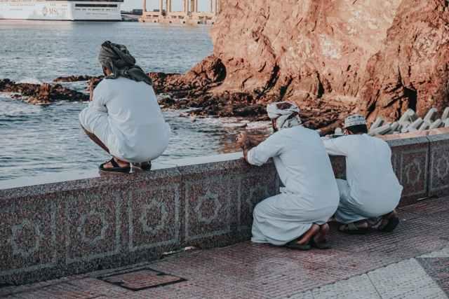 arab men in white traditional wear praying on embankment