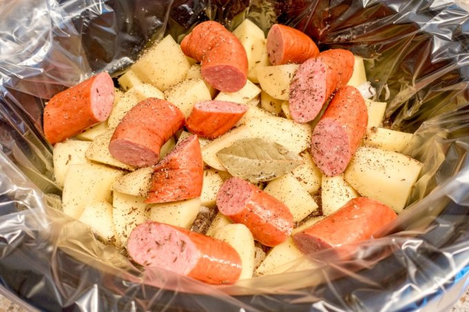 Kielbasa and sauerkraut plus potatoes and other ingredients in the pot for slow cooking