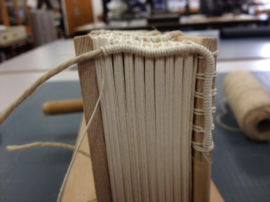 woven headband on wooden coverboards for medieval book
