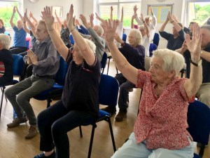 Older adults in their chairs exercising
