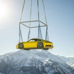 Porsche 911 dropped off by helicopter at a spectacular alpine resort