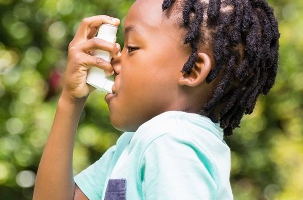 A little girl using an inhaler due to her asthma condition.