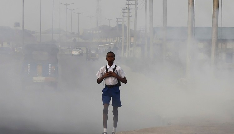 A school boy walks past smoke and fumes emitted from a dump in the city of Port Harcourt, Rivers State, on February 14, 2017. Credit: PIUS UTOMI EKPEI/AFP/Getty Images)