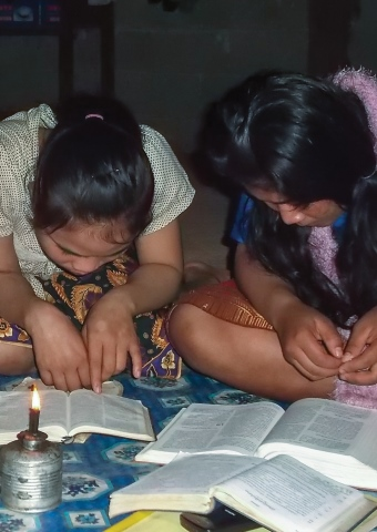 Two young Lao girls read Bibles. Pray for those who have been rejected by their families.