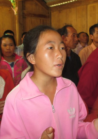 A woman worshiping at a church service in Laos.