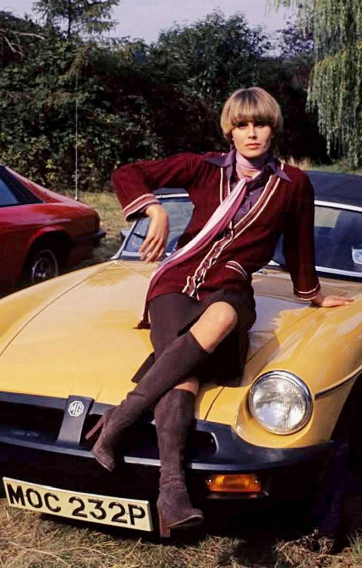 La actriz y presentadora británica Joanna Lumley sobre un MGB a mediados de los años 70