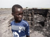 A child stands in front of his burned home in Leer, South Sudan on Saturday, May 23, 2015. /CC BY-NC-ND/ICRC/P. Krzysiek