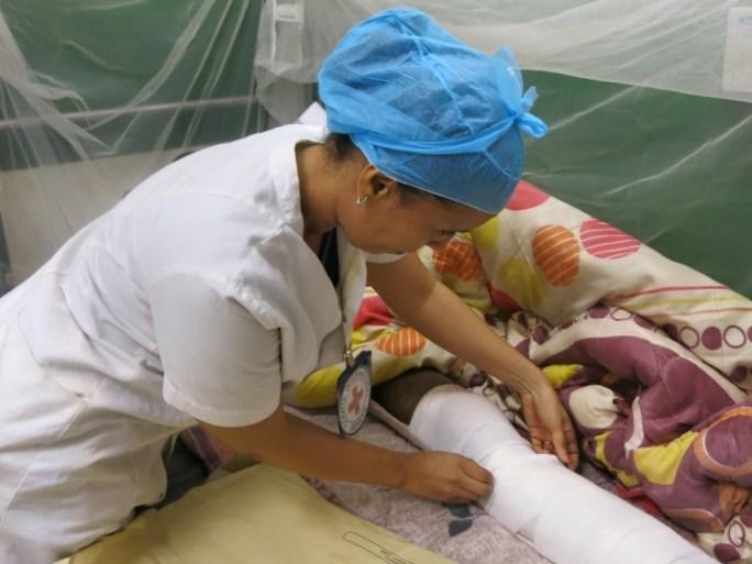 Azahara ajuste le pansement d'un patient qui se remet d'une opération.