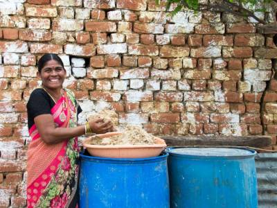 Yaadamma, who heads a women's self-help group in Fasalvadi, holds some of the malt she collects and sells at her home. Photo: S. Punna/ICRISAT