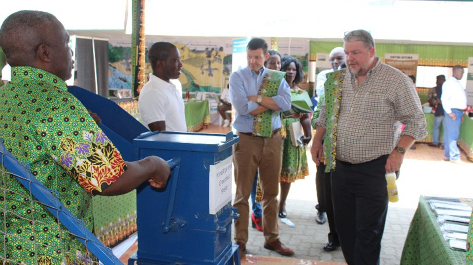 Cullen Hughess, Director of Sustainable Economic Growth (center) and Peter Trenchard, USAID Acting Mission Director to Malawi (right) listen as an ICRISAT officer (left) explains the working of a machine. Photo: L Lazarus, ICRISAT