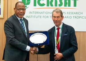 Dr Paco Sereme presenting a plaque to Dr Nigel Kerby. Photo: PS Rao, ICRISAT