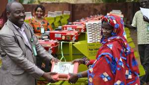 Dr Ayoni Ogunbayo, Country Project Manager, Mali, presents a shelling machine to Mrs Mariam Coulibaly.