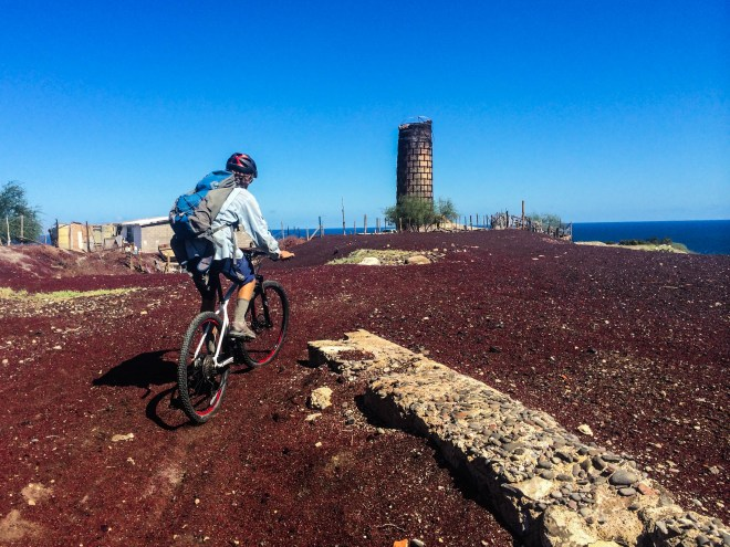 Josh rides out onto the flattened top of the tierra quemada cone, the red remnants of El Boleo Copper Company mine. The brick smokestack from the smelter stands at the edge of the pile.