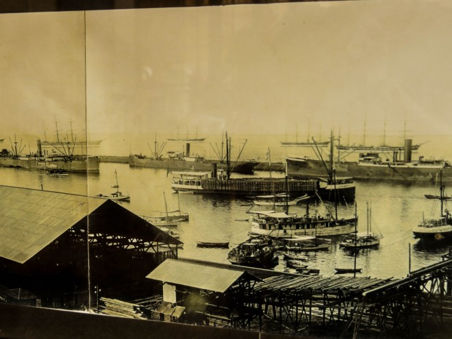 A photo of the harbor from the turn of the 20th century. Mexican-built steam ships designed to cross the Sea of Cortez sit in the harbor, and international sailing ships sit outside the breakwater wall, waiting to offload giant wooden beams and take on the mined copper.