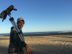 Luis Morales, with his bird spotting scope, tunes into his local birds in the morning's first sun.