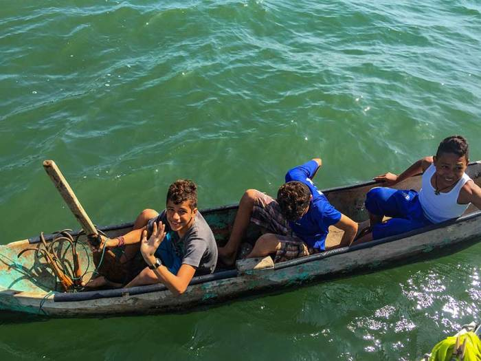 The canoe and paddles are rough, but the three boys make it work—though not without plenty of giggling.