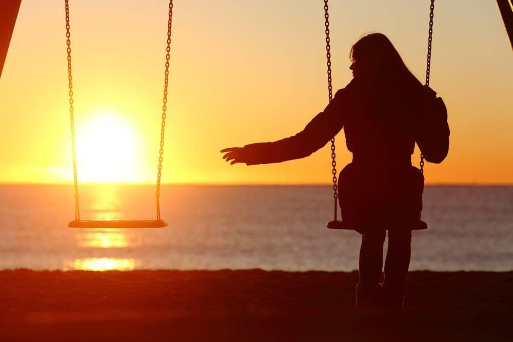 Woman sitting on a swing reaching out for empty swing with sunset in background