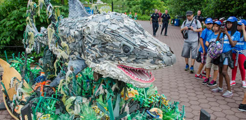A large sculpture of a shark made out of plastic waste found in the ocean.