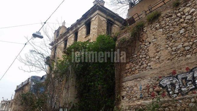 Το πέτρινο σπίτι από την πλαϊνή πλευρά με γκράφιτι στο κάτω μέρος.