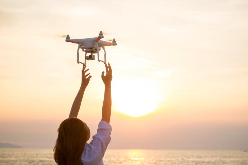 Μία γυναίκα πιάνει ένα drone που είναι στον αέρα.