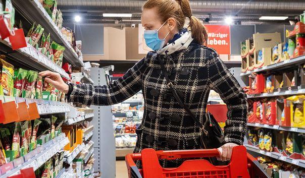 Frau kauft Lebensmittel im Supermarkt während Covid-19 Pandemie