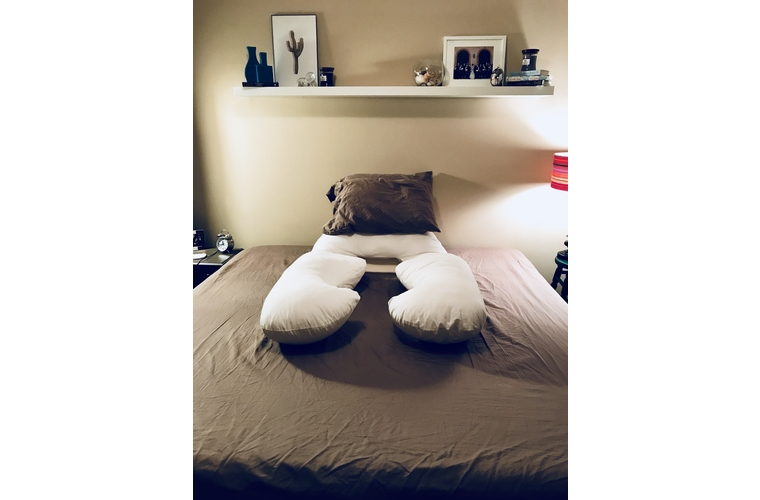 Bed with body pillow wedge and pillows for mastectomy recovery