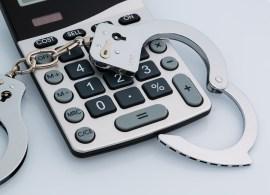 calculators and handcuffs on a white background. representative