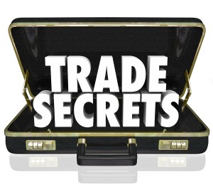 The words Trade Secrets in an opening black leather briefcase to