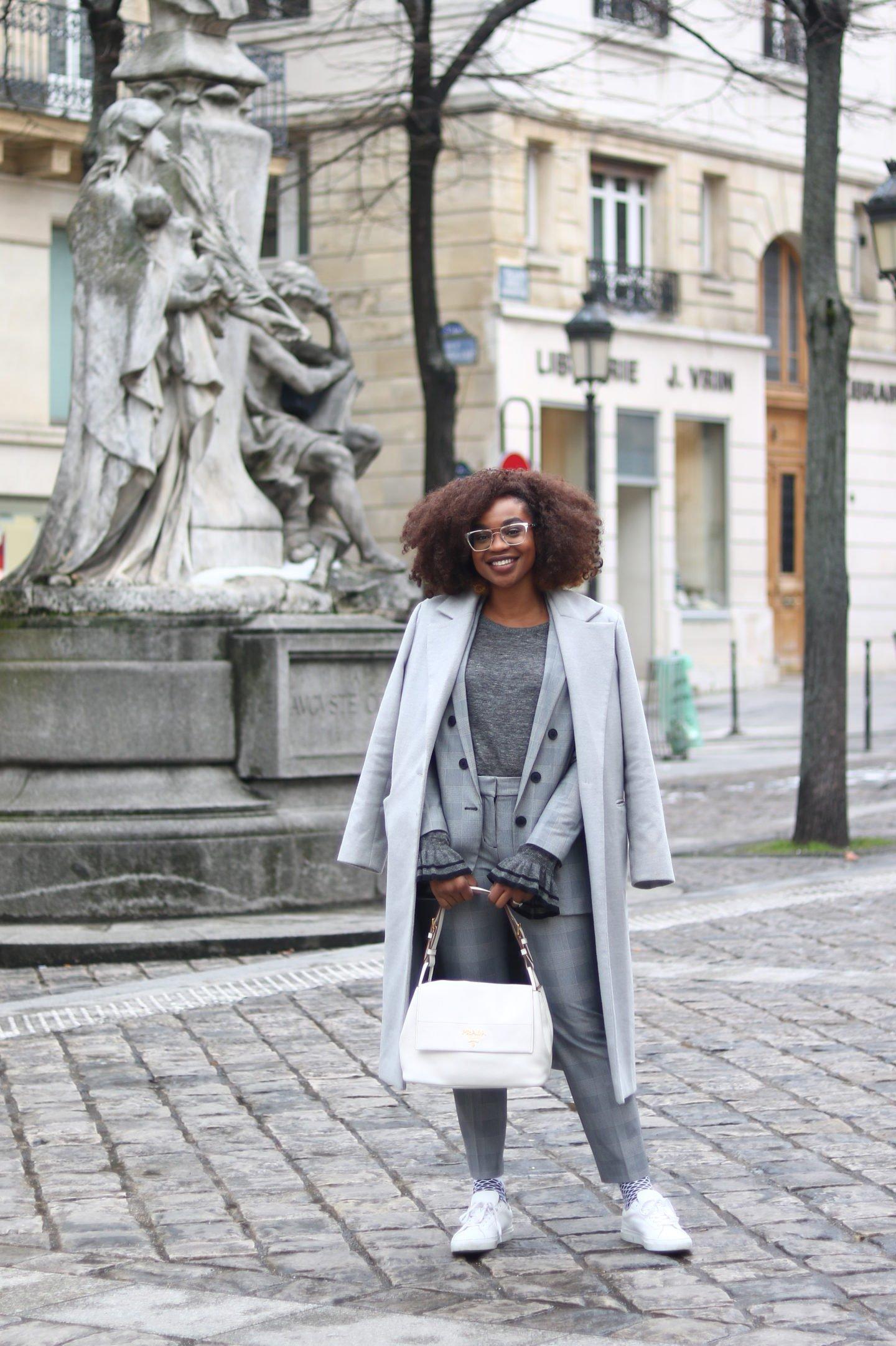 Fashion blogger Ijeoma Kola wears monochrome gray check suit with white sneakers for Paris Fashion Week