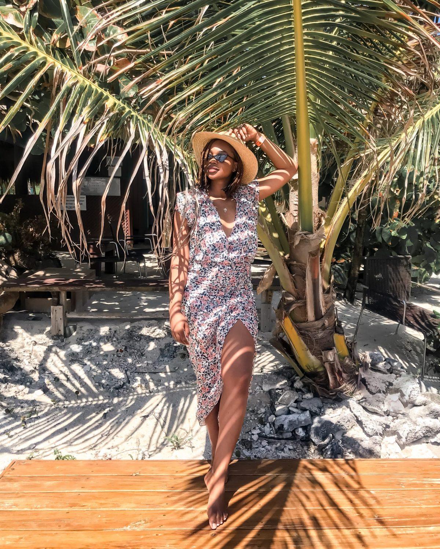 Blogger Ijeoma Kola wears veronica beard brynlee dress and straw hat on big french key in roatan honduras