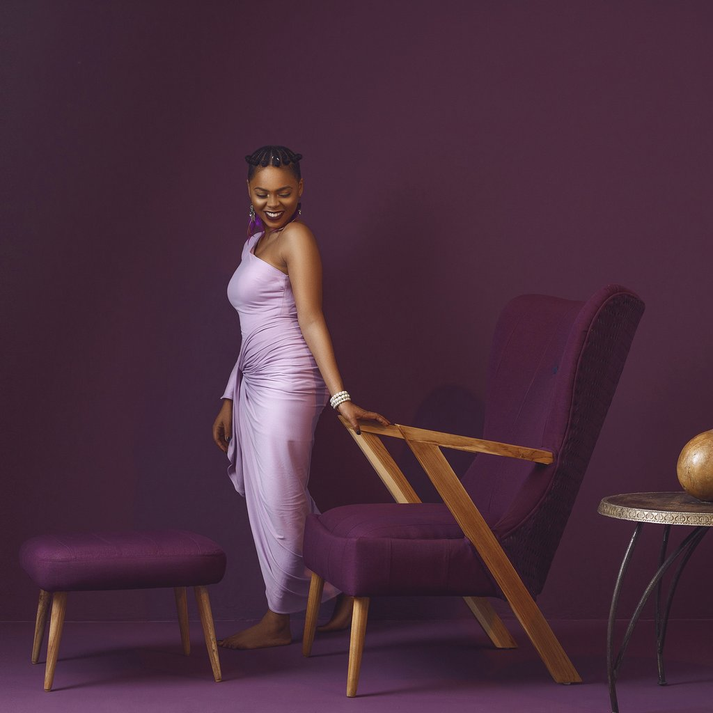 Black model in purple dress in purple doom with purple furniture