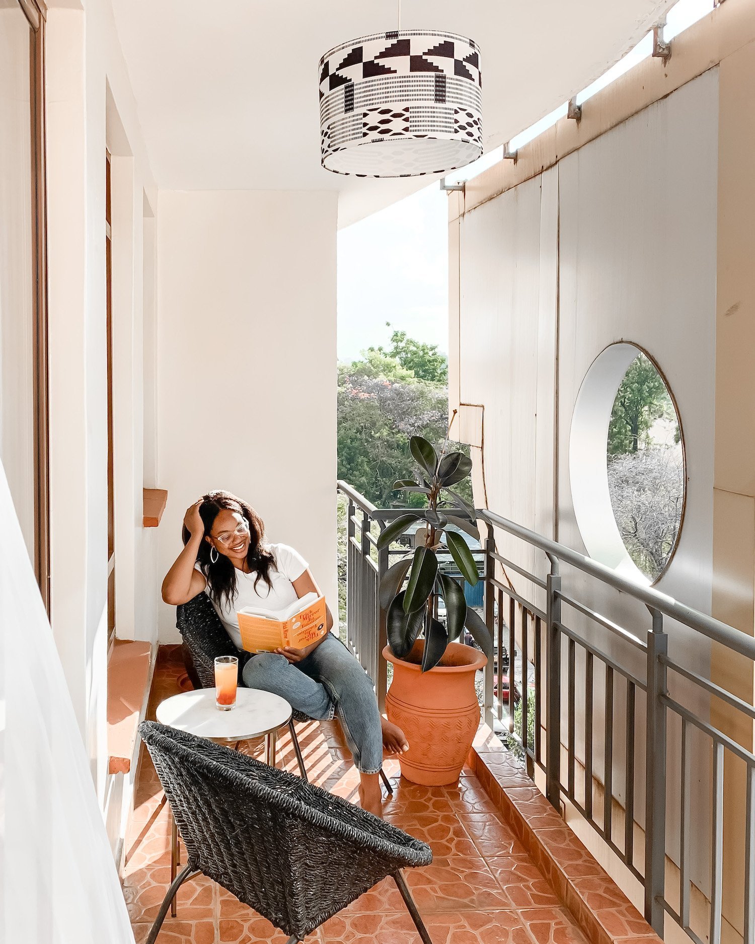 Ijeoma Kola reading book on balcony with decor from Black owned home decor brands