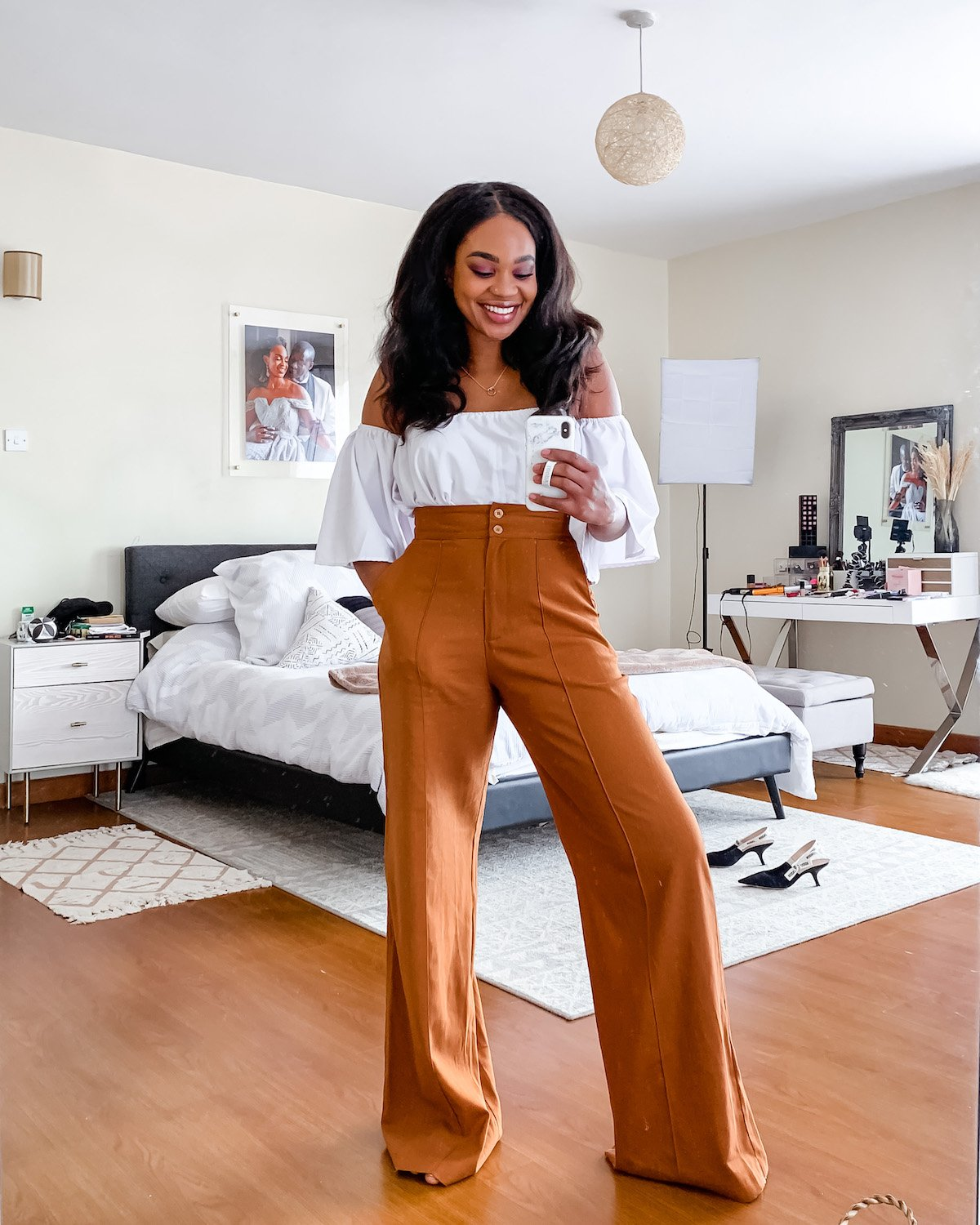 Ijeoma Kola in white off-the-shoulder top and brown wide leg pants from black owned fashion brands