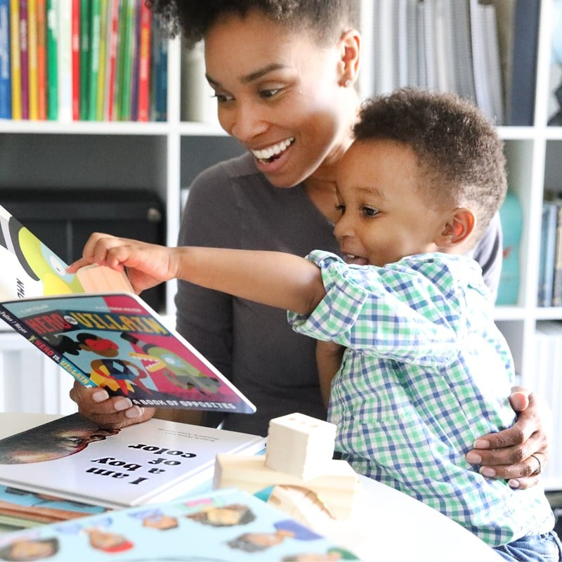 Black mom and son reading book with black characters
