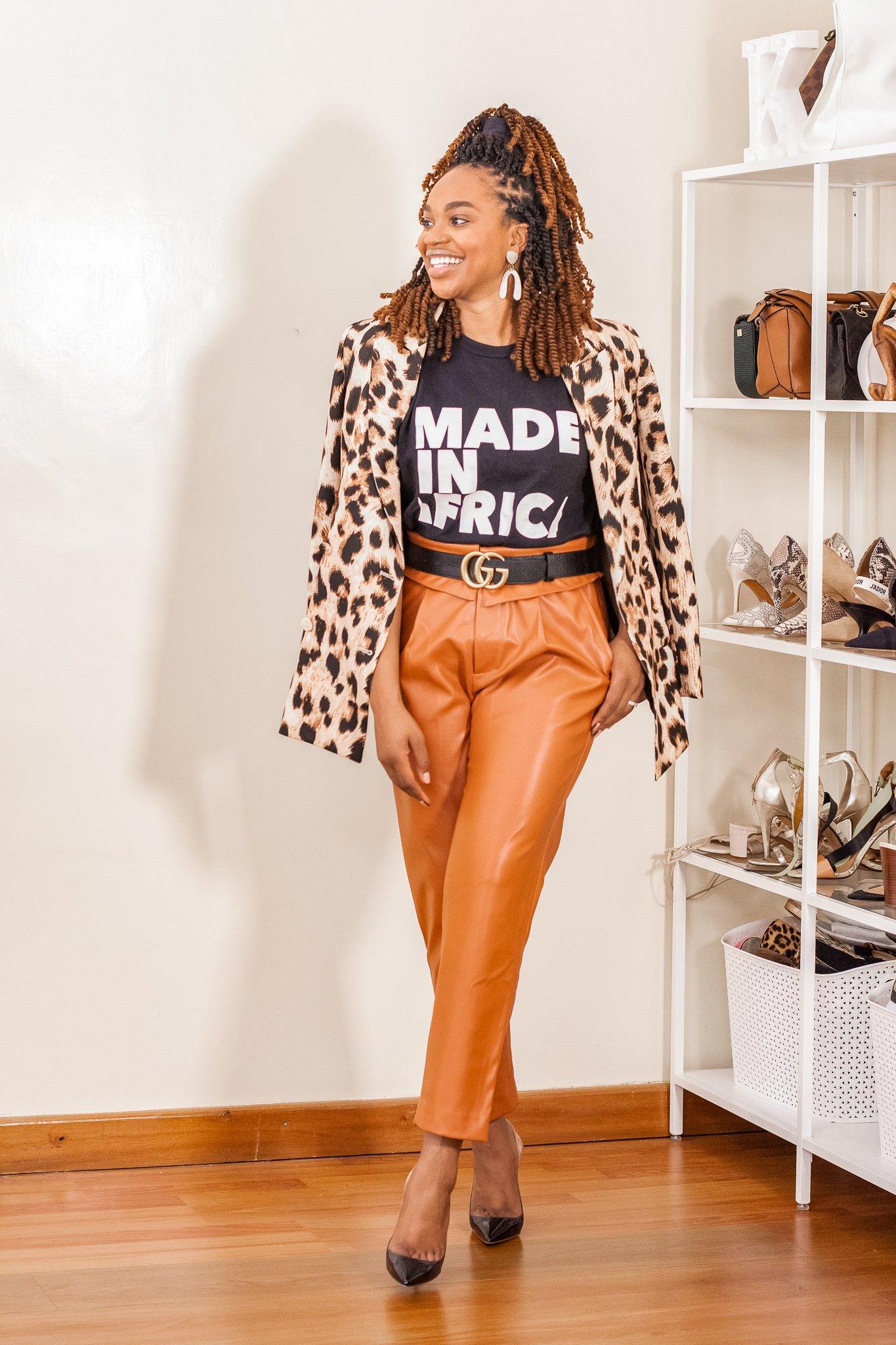 Ijeoma Kola in leopard print stylish blazer, back t-shirt, orange leather pants, and black stilettos.