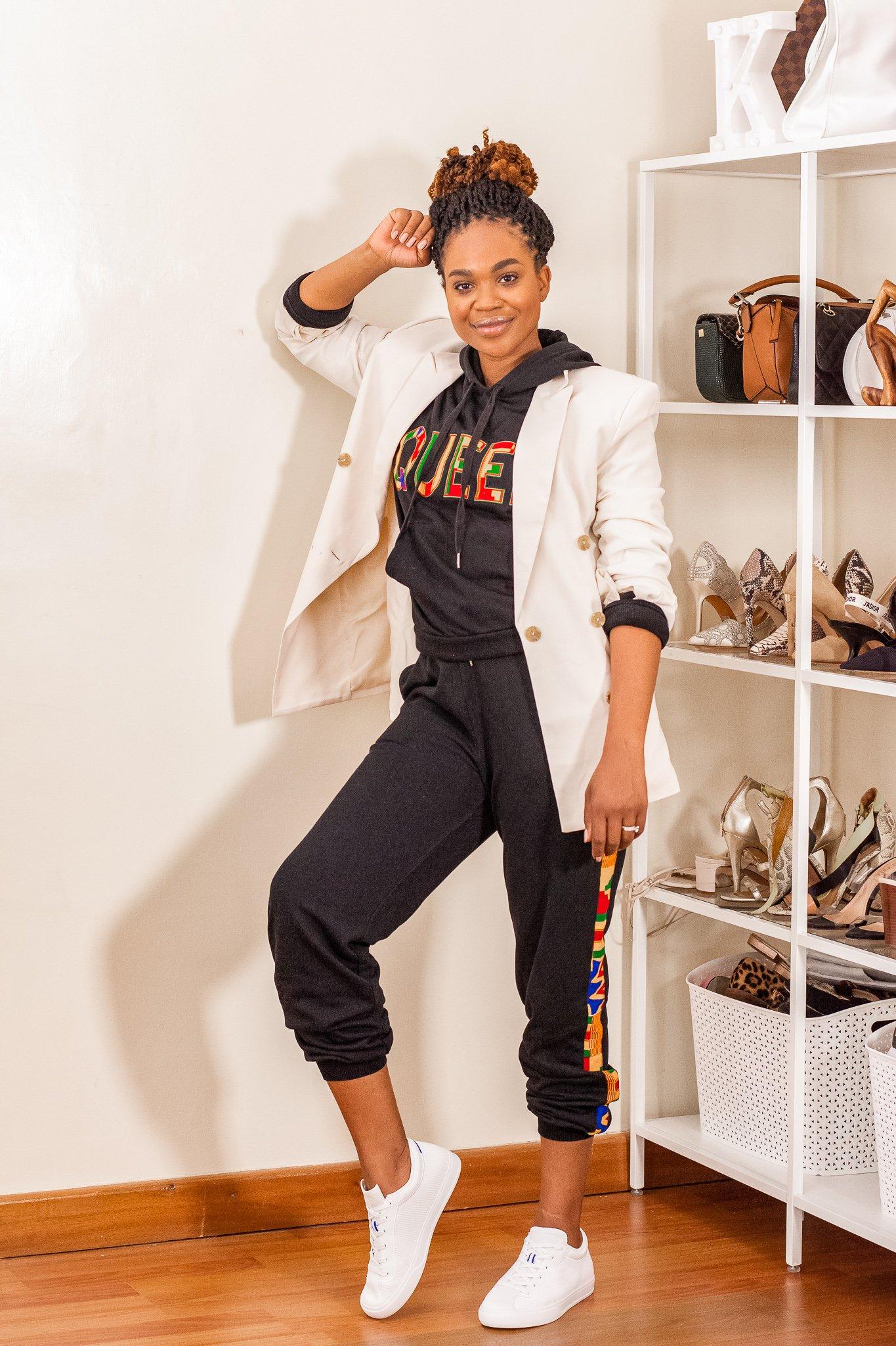 Ijeoma Kola in cream stylish blazer, dark grey jumpsuit with print, and white sneakers.