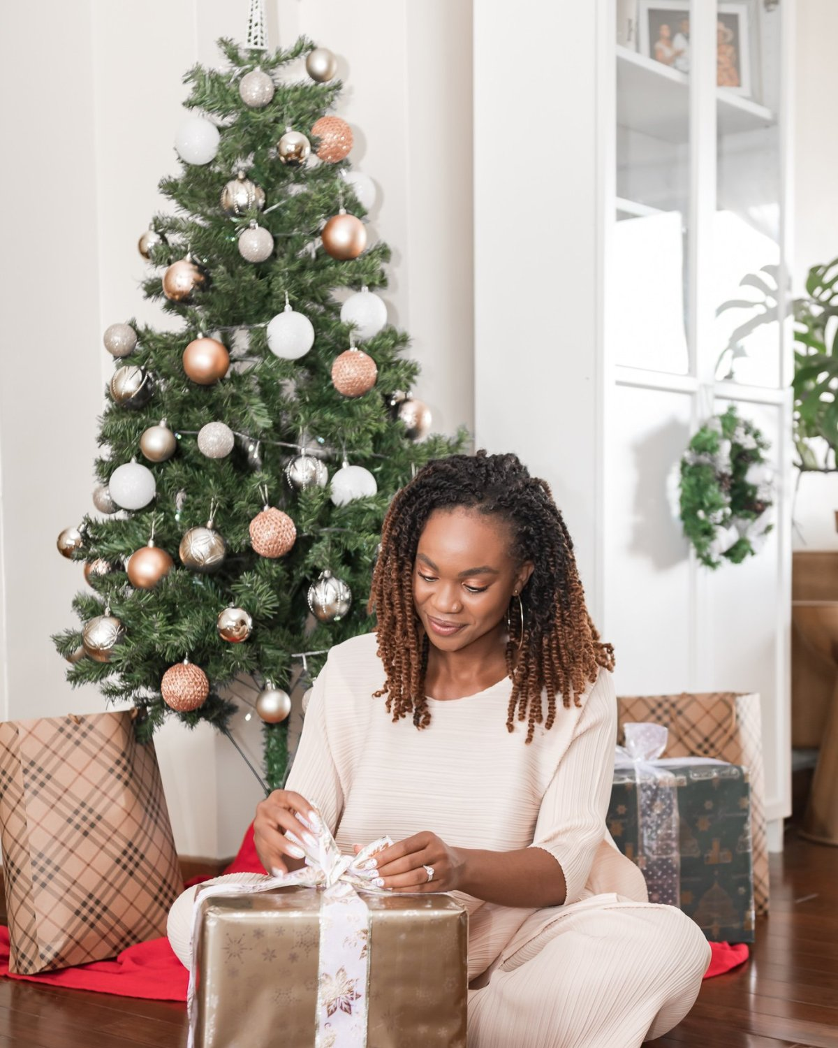 Ijeoma Kola untying bow on gold box in front of decorated Christmas tree