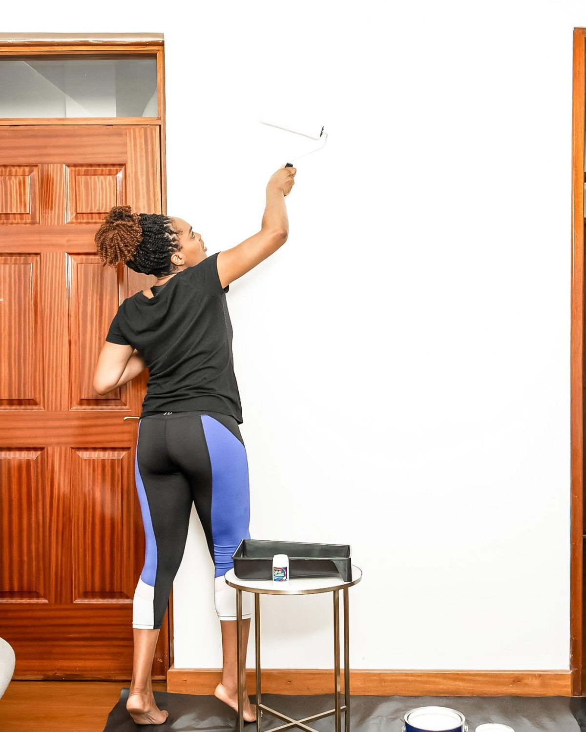 Ijeoma Kola painting a white wall to demonstrate one of her easy room makeover ideas
