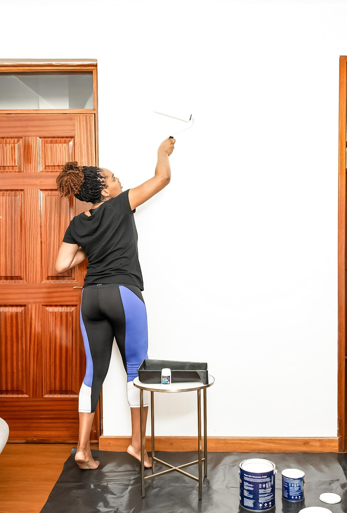 伊耶玛·科拉painting a white wall to demonstrate one of her easy room makeover ideas