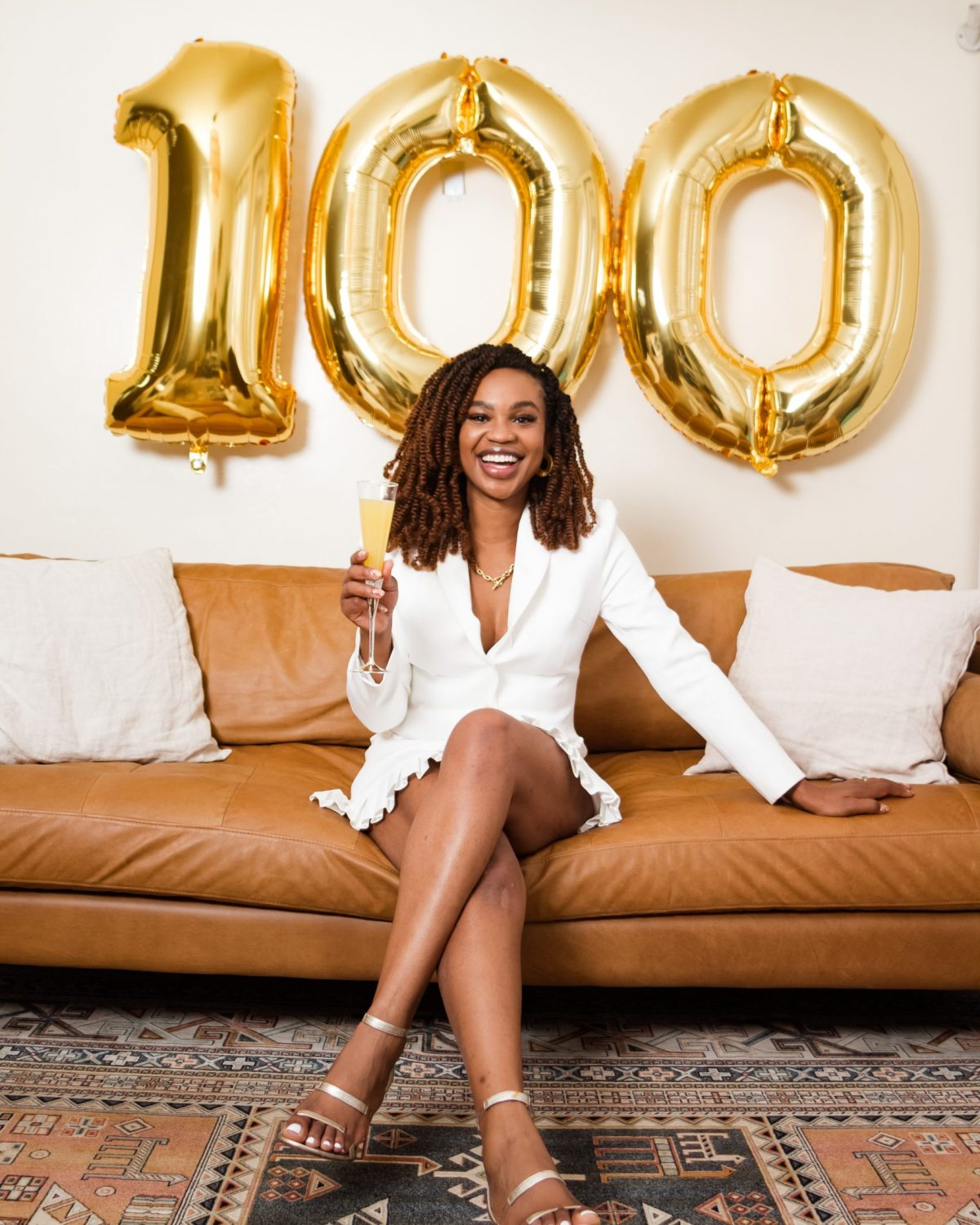 Ijeoma Kola in white blazer dress posing on couch