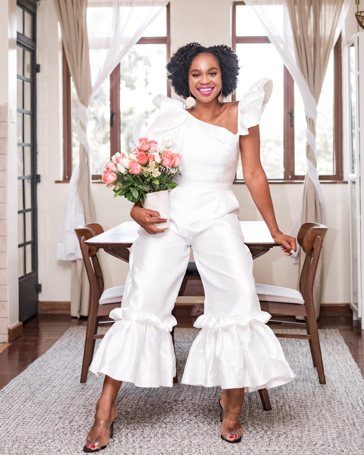 Ijeoma Kola in white outfit and flowers in a bouquet