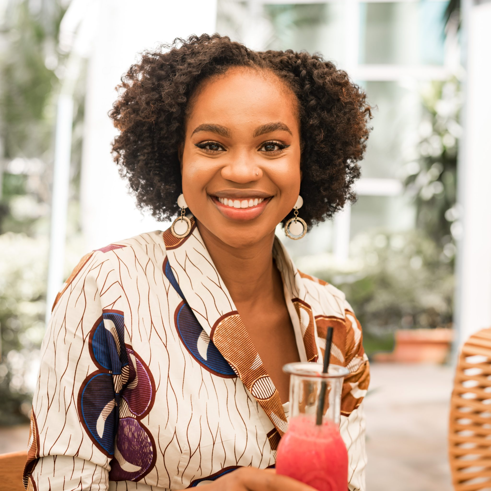 Ijeoma Kola in African print dress and twist out, smiling and drinking a cocktail