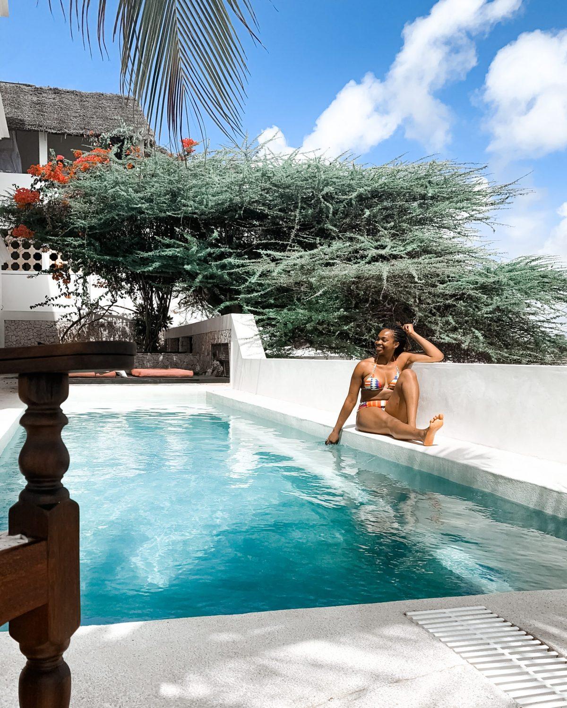 Ijeoma Kola posing poolside in a bikini - 2021 Travel Destinations Buck List Blog