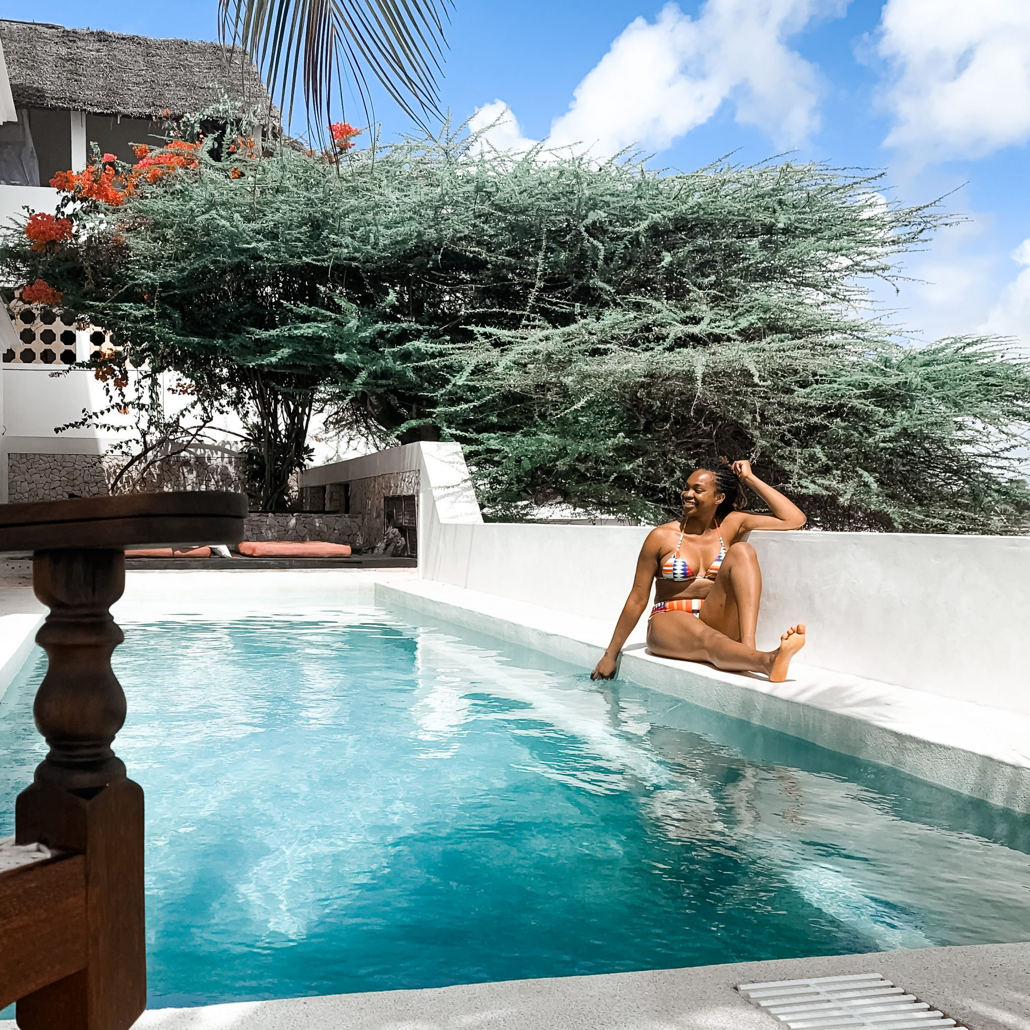 Ijeoma Kola posing poolside in a bikini - 2021 Travel Destinations Buck List Blog