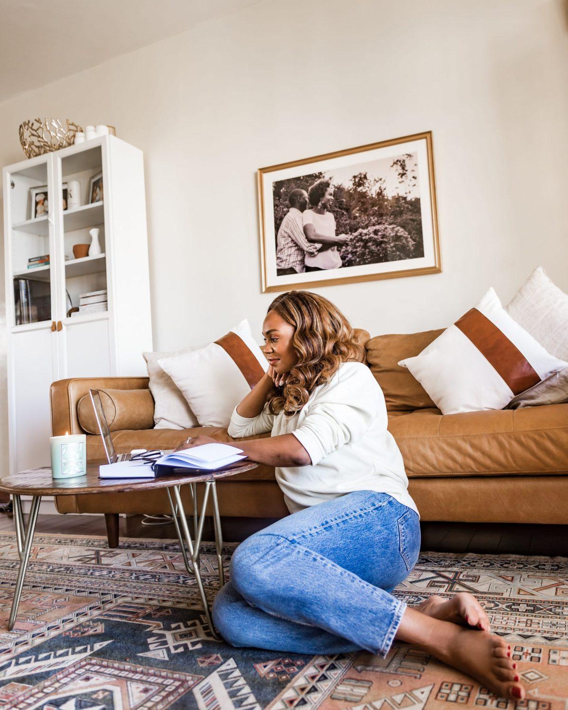 Ijeoma Kola scrolling on laptop while sitting on living room floor - 2021 resolutions blog